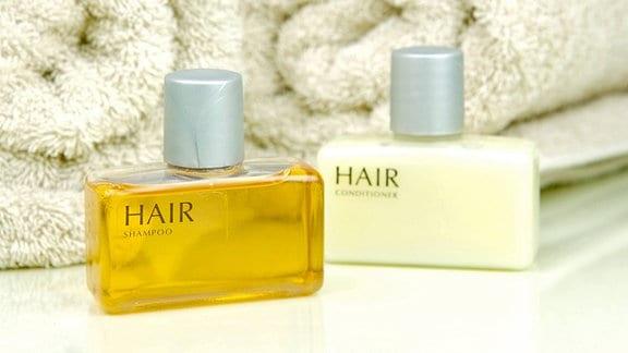 Shampoo und zusammengerollte Handtücher