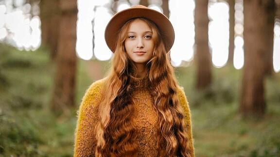 Eine Frau mit Hut steht in einem Wald