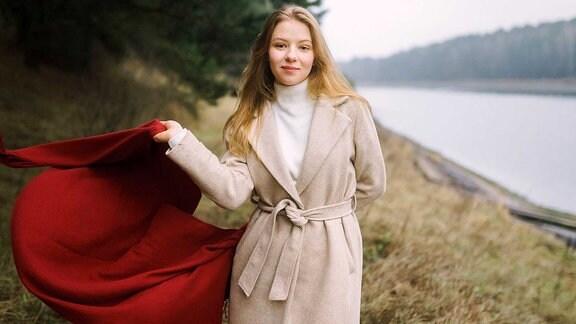 Eine Frau mit einem großen roten Schal steht an einem Fluss.