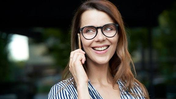 Junge, geschminkte Brillenträgerin mit einem Telefon am Ohr