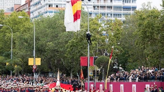 Fallschirmspringer hängt an Laternenmast während einer Militärparade.