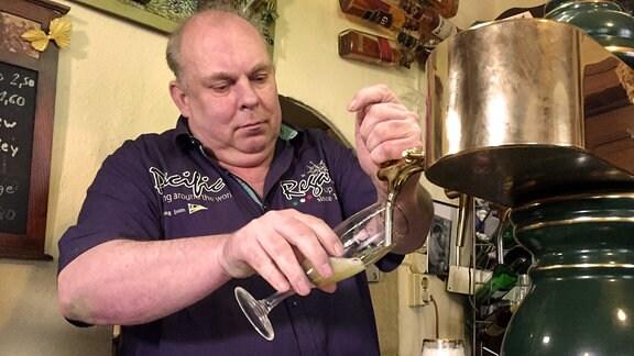 Ein Kneipenwirt zapft Bier.