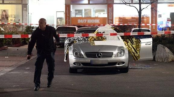 Ein Polizist geht neben einem mit Thermofolie abgedeckten Auto unter Absperrband her.