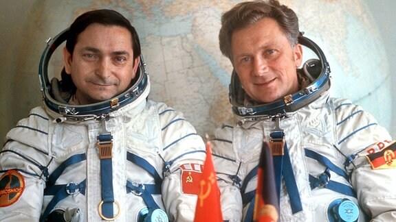 Das Foto zeigt den russischen Kosmonauten Waleri Bykowski (l) und den deutschen Kosmonauten Sigmund Jähn, die in ihren Raumanzügen vor einem großen Globus sitzen.