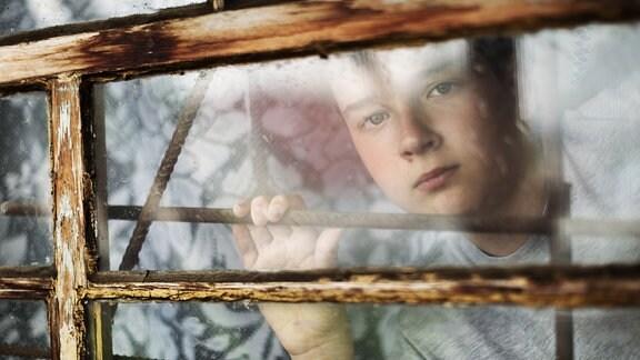 Ein Junge schaut traurig aus einem Fenster