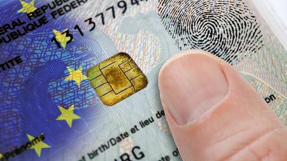 Finger auf deutschem Personalausweis mit EU-Fahne, Datenchip und Fingerabdruck