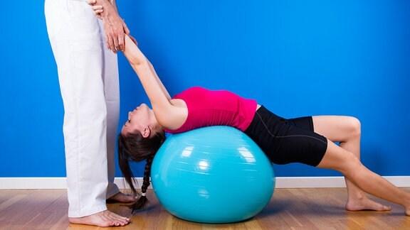 Frau liegt auf Gymnastikball