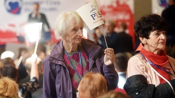 Eine ältere Frau hält ein Fähnchen hoch.