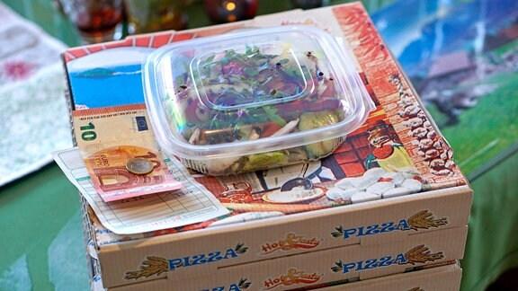 Ein Salat, eine Rechnung und Geld liegen auf gelieferten Pizzakartons