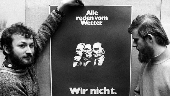 Ulrich Bernhardt vom SDS und ein weiterer Student halten 1968 das rote SDS-Plakat in die Höhe, das neben dem Werbespruch 'Alle reden vom Wetter - Wir nicht' die Köpfe von Marx, Engels und Lenin zeigt.