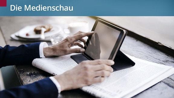 Ein Mann im Anzug sitzt am Frühstückstisch. Er tippt auf einem Tablet und liest Zeitung.