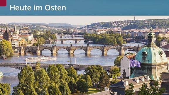 Prag von oben. Man sieht viele Brücken über Moldau und ein Kuppelgebäude, auf dem eine Europa-Flagge weht.