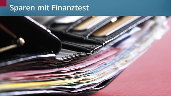 Ein prall gefülltes Portmonee liegt offen auf einem Tisch. Viele Geldscheine und Kreditkarten schauen heraus.