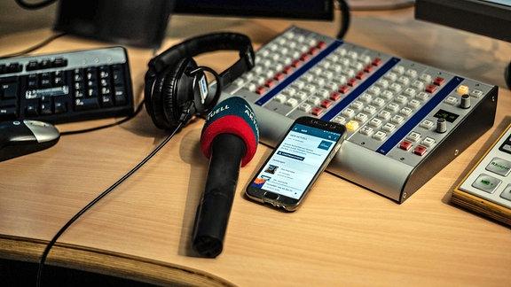 Ein Mikrofon von MDR AKTUELL im Studio, daneben ein Handy/Smartphone