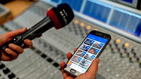 Ein Mikrofon von MDR AKTUELL und ein Handy/Smartphone mit ARD Audiothek in der Hand