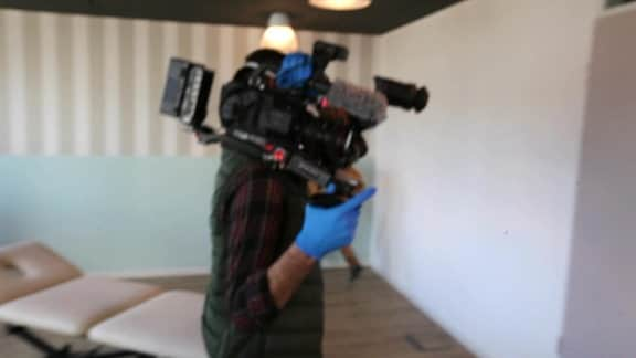 Ein Kamermann mit Handschuhen schuktert eine Kamera
