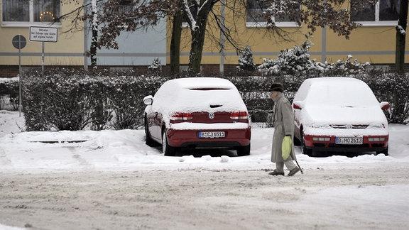 Rentner läuft vorsichtig auf einer verschneiten Straße.