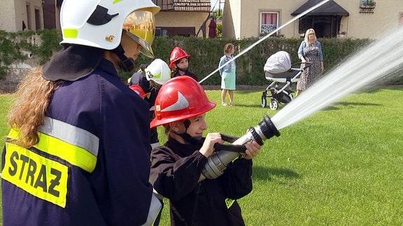Mädchen in Feuerwehruniformen mit Löschspritzen