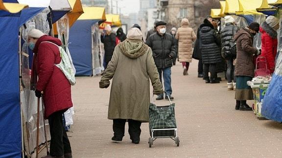 Eine Seniorin zieht einen Einkaufswagen über einen Markt.