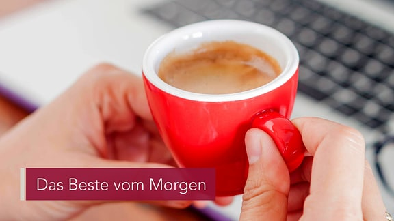 Jemand hält eine rote Espresso-Tasse in der Hand. Der Kaffee dampft. Auf einem Tisch liegen ein Laptop und eine Brille.