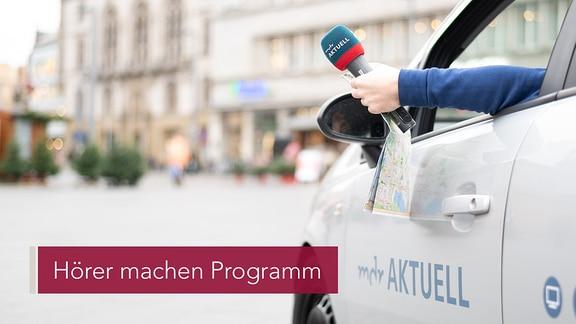 Ein Arm hält ein Mikrofon und lehnt aus einem Auto heraus.