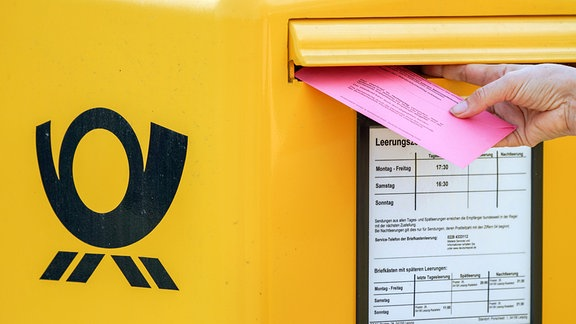Einen Briefwahlumschlag zur Bundestagswahl 2021 steckt eine Frau in einen Briefkasten.
