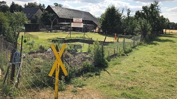 Ortseingang des Dorfes Mühlrose mir gelbem Holzkreuz eines Umsiedlungsgegners