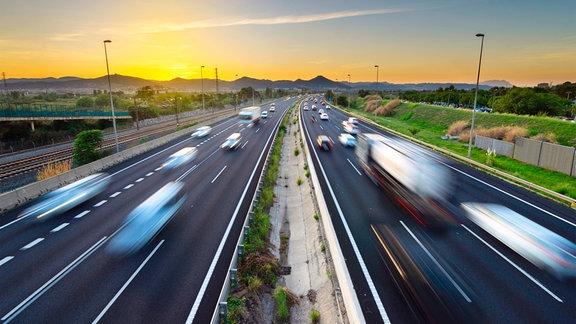 Vielbefahrene Autobahn in Spanien während des Sonnenuntergangs.