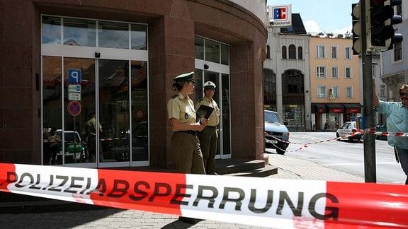 Polizeibeamte sichern den Tatort am Rande eines Raubüberfalls auf eine Sparkasse