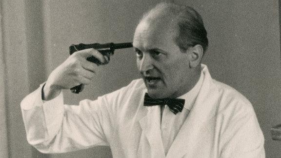 Mann in weißem Kittel mit Fliege hält sich einen Revolver an die rechte Schläfe