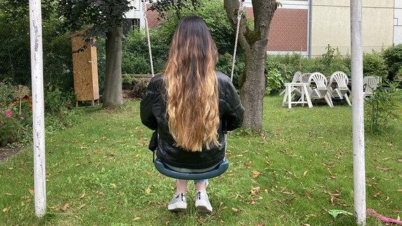 Elli sitzt mit dem Rücken zum Betrachter auf einer Schaukel.