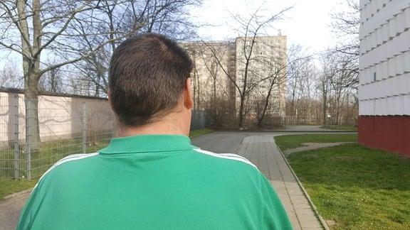Ein Mann im grünen Shirt von hinten.