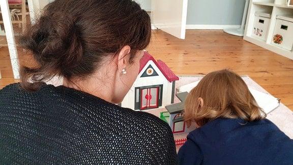 Eine junge Frau spielt gemeinsam mit ihrer Tochter im Kinderzimmer.
