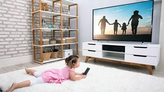 Kind liegt vor einem Fernseher.