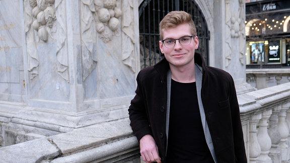 Junger Mann mit Brille lehnt an einem steinernen Geländer