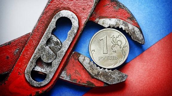 Ein-Rubel-Münze vor russischer Fahne in der Zange