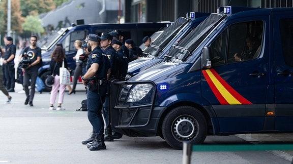 Polizisten stehen in Barcelona vor ihren Fahrzeugen.