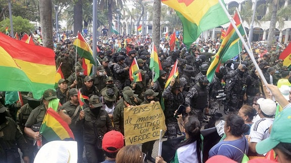 Polizisten schwenken die dreifarbige Flagge Boliviens, während sie sich in eine Polizeistation in der Stadt Santa Cruz zurückziehen.