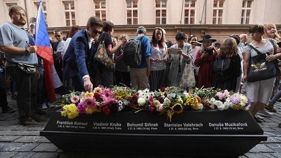 Eine Menschenmenge steht um einen schwarzen Sarg mit Blumen.