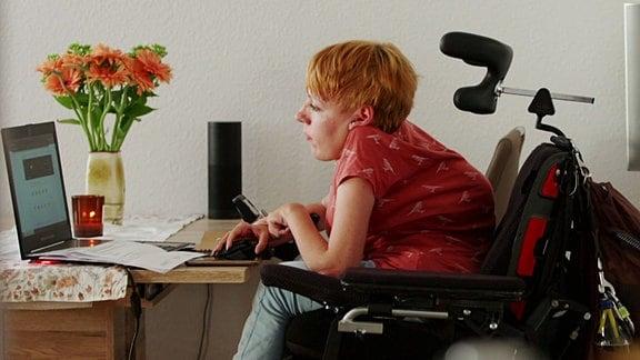 Eine Frau sitzt an einem Schreibtisch mit einem Laptop.