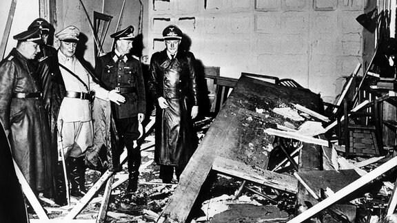 """Reichsmarschall Hermann Göring und der Chef der """"Kanzlei des Führers"""", Martin Bormann, begutachten die Zerstörung im Raum der Karten-Baracke im Führerhauptquartier Rastenburg."""