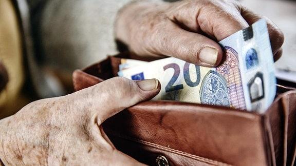 Seniorin zieht einen 20 Euro Schein aus ihrem Portemonnaie