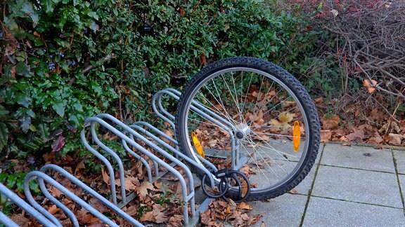 Abgeschlossenes Vorderrad einen Fahrrades steckt in einem Fahrradstaender
