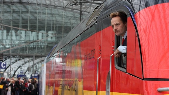 okführer schaut aus dem Fenster eines Zuges.