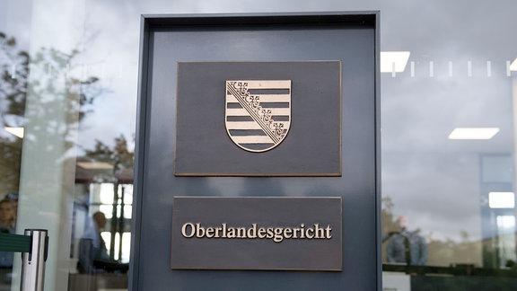 Justizbeamte stehen im Eingangsbereich des Prozessgebäude des Oberlandesgerichts Dresden.