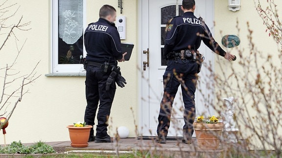 Zwei Polizisten in Uniform stehen vor der Haustür