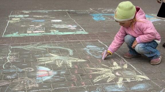 Ein kleines Kind malt mit Kreide auf der Straße