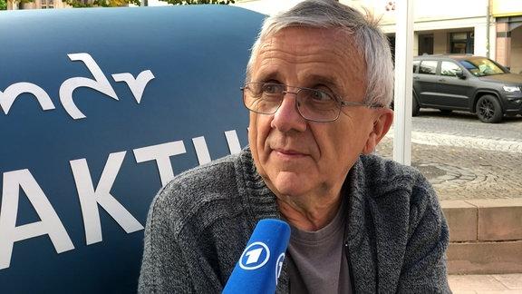 männlicher Interviewpartner mit Mikrofon