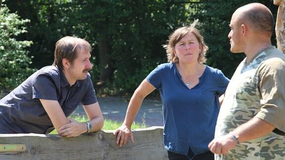 Grit Herzog unterhält sich mit zwei Männern.