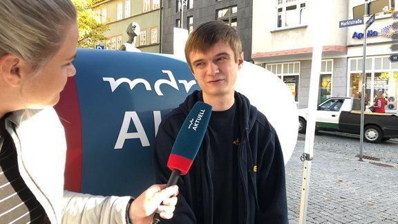 Ein junger Mann nah spricht in ein Mikrofon.